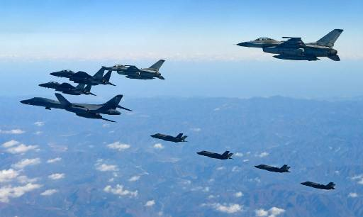 This handout taken and released by the South Korean Defence Ministry in Seoul on December 6, 2017 shows a US Air Force B-1B Lancer bomber (L), two US F-35A and two US F-35B stealth jets (far) flying over South Korea with South Korea's two F-16 (R) and two F-15K (L top) fighter jets during a joint military drill. The five-day Vigilant Ace drill -- involving some 230 aircraft including F-22 Raptor stealth jet fighters -- began on December 4, five days after North Korea test-fired an intercontinental ballistic missile believed to be capable of hitting the US mainland in a new challenge to US President Donald Trump.