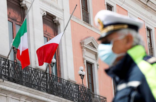 The flags of Italy and Bari flutter to half mast to honor the country's dead due to COVID-19, in Bari, Italy, on Tuesday.