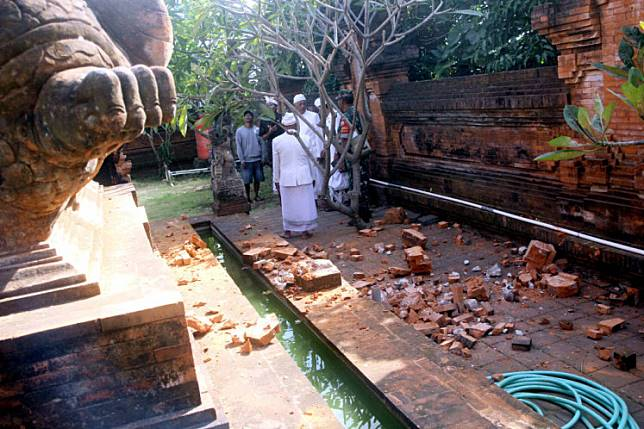 Priests assess damage at the Pura Lokananta temple in Denpasar, Bali, after a 5.8-magnitude earthquake struck the island on July 16.