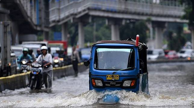 Sebuah bajaj menerobos banjir di Jalan Letjen Suprapto, Jakarta Pusat, Sabtu (8/2/2020). [Antara/Sigid Kurniawan]