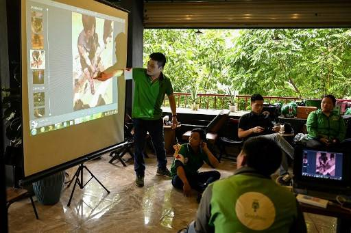 This photograph taken on May 7, 2020 shows Grab motorcycle rider Pham Quoc Viet (left) teaching first aid to Grab riders during his SOS Angels class in Hanoi. By day, Pham Quoc Viet, 33, works as a motorcycle taxi driver for Southeast Asian ride-hailing firm Grab, scooting along the tree-lined boulevards and winding alleys of the city. But from 9.30 pm until 1.30 am, he is an unofficial emergency responder, a red flashing light secured to his handlebars as he patrols the streets on two wheels searching for traffic accident victims.