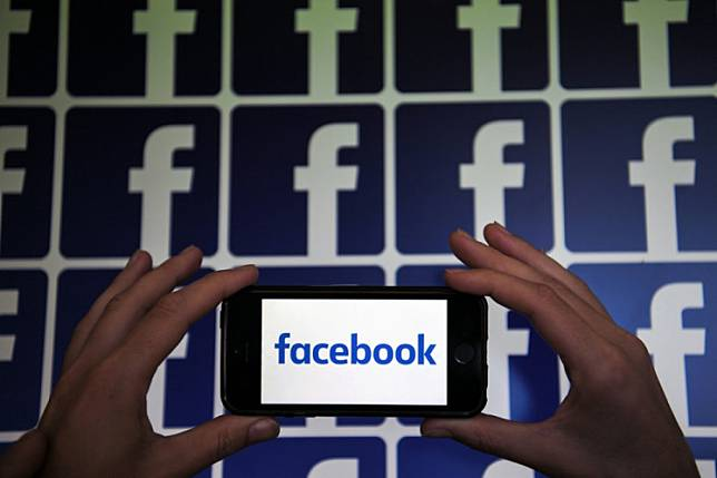 A person shows the logo of the US online social media and social networking service, Facebook on a smartphone, on July 4, 2019 in Nantes.