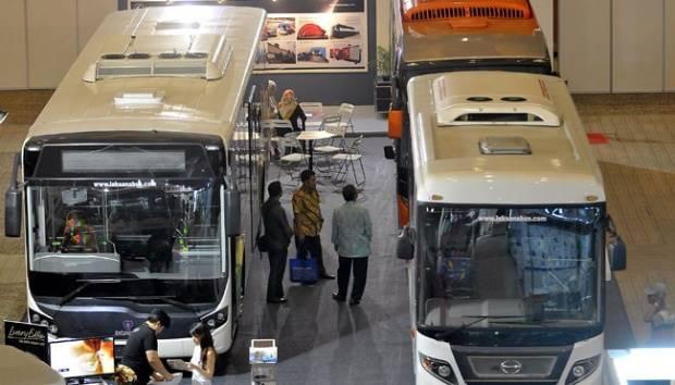 Pengunjung mengamati bus yang dipamerkan dalam pameran tahunan industri komponen otomotif, aksesoris kendaraan, serta industri pendukung, di Jakarta International Expo (JIExpo), Kemayoran, Jakarta, 29 Maret 2016. TEMPO/Tony Hartawan