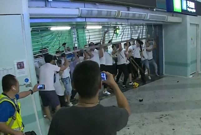 白衣人扯開港鐵車站鐵閘。港台影片截圖