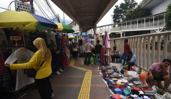 Warga melihat barang dagangan yang dijual pedagang kaki lima (PKL) di trotoar Tanah Abang
