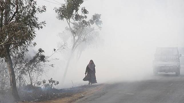 A woman walks along the road covered in smog due to the forest fire in Banjarbaru, South Kalimantan province, Indonesia, September 6, 2019. Picture taken September 6, 2019. Fires have burnt through parts of Sumatra and Borneo island for more than a month and the government has sent 9,000 military, police and disaster agency personnel to fight the flames. Antara Foto/Bayu Pratama S via REUTERS