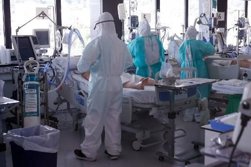 Healthcare workers wearing protective suits attend to COVID-19 coronavirus patients at the Intensive Unit Care (ICU) of the Vall d'Hebron Hospital in Barcelona on April 6, 2020.