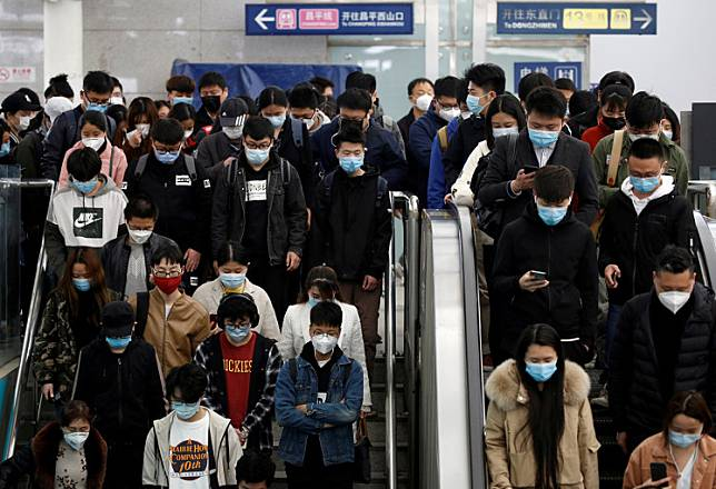 People wearing face masks stand on an escalator inside a subway station during morning rush hour in Beijing, as the spread of the COVID-19 continues in the country, in China on Tuesday. China reported no new coronavirus deaths for the first time since January..