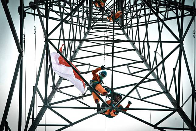 State-owned electricity company PLN workers conduct maintenance on a transmission tower.