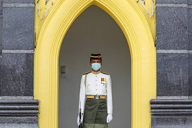 A Malaysian Royal Guard wears a protective mask while he stands guard outside National Palace in Kuala Lumpur, Malaysia, on Feb. 10, following the outbreak of the COVID-19 coronavirus in China.