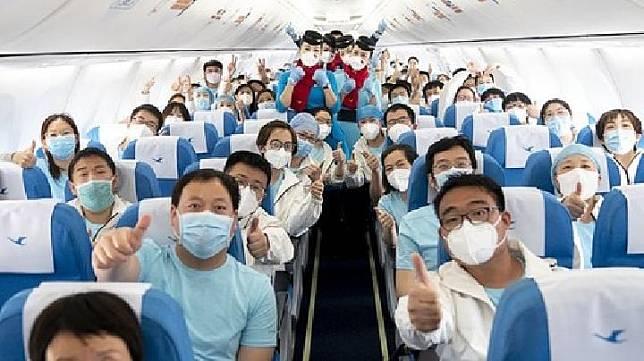 Para perawat dari Kota Tianjin mengacungkan ibu jari sebagai salam perpisahan sebelum meninggalkan Wuhan, Provinsi Hubei, Cina, 17 Maret 2020. Mereka telah bekerja untuk merawat pasien Corona hingga merelakan waktu libur Imlek mereka bersama keluarga. Xinhua/Xiao Yijiu