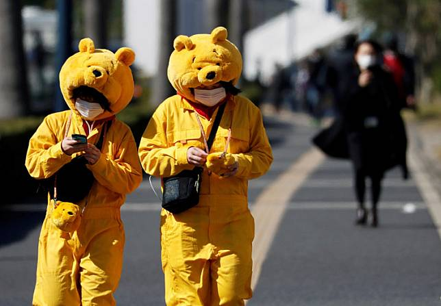 Visitors wearing protective face masks and Winnie the Pooh costumes, following an outbreak of the coronavirus, are seen outside Tokyo Disneyland in Urayasu, east of Tokyo, Japan February 28, 2020.