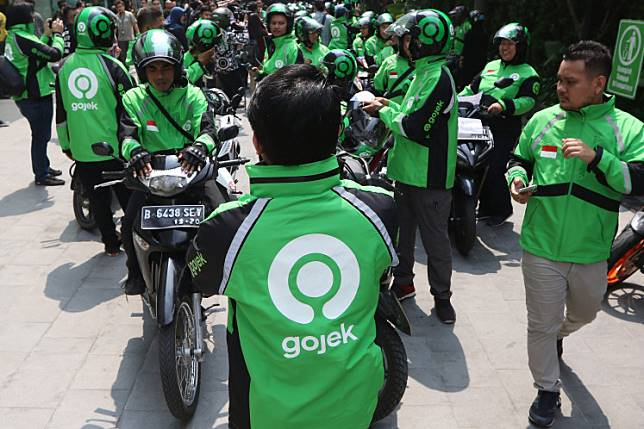 Go-Jek drivers wear their jackets with new logo on Monday. Go-Jek's new logo  (nicknamed 'Solve') symbolizes a map pin, a motorcycle wheel and an eagle-eye view of a driver straddling a motorcycle.