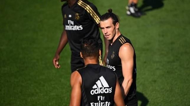 Pemain Real Madrid Gareth Bale (tengah) berbincang dengan rekannya di tengah sesi latihan Real Madrid di Real Madrid Sports City [AFP]