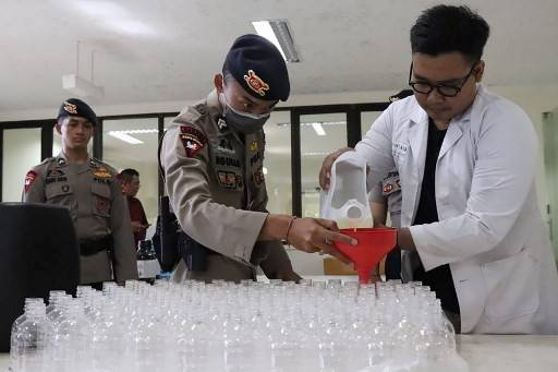 This handout photo taken taken on April 2, 2020 and received from Bali Police on Wednesday shows a policeman  and Udayana University researcher making hand sanitizer from donated palm wine, known locally as arak, in Denpasar.  Pharmacists on the Indonesian holiday island of Bali are tackling a shortage of anti-coronavirus hand sanitizer by making their own unique, tropical version -- from thousands of liters of fermented palm wine.