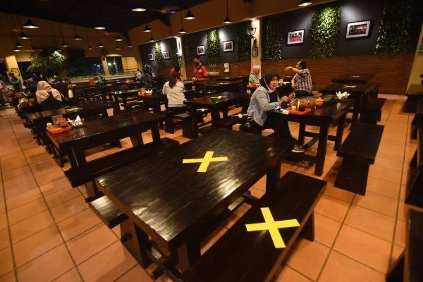 Pengunjung menyantap hidangan di antara meja yang diberi tanda silang di restoran di Srengseng Sawah, Jakarta Selatan