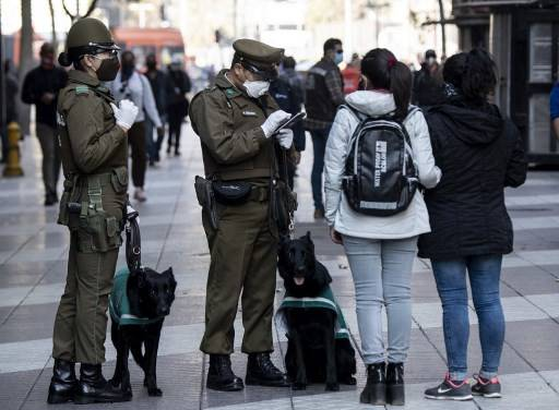 Police member check two passers-by at Plaza de Armas square, in Santiago, on May 13, 2020, after the government ordered a mandatory total quarantine due to the COVID-19 pandemic. Chile registered a new high for coronavirus cases on Monday, with nearly 5,000 infections in 24 hours, including two ministers in President Sebastian Pinera's government.
