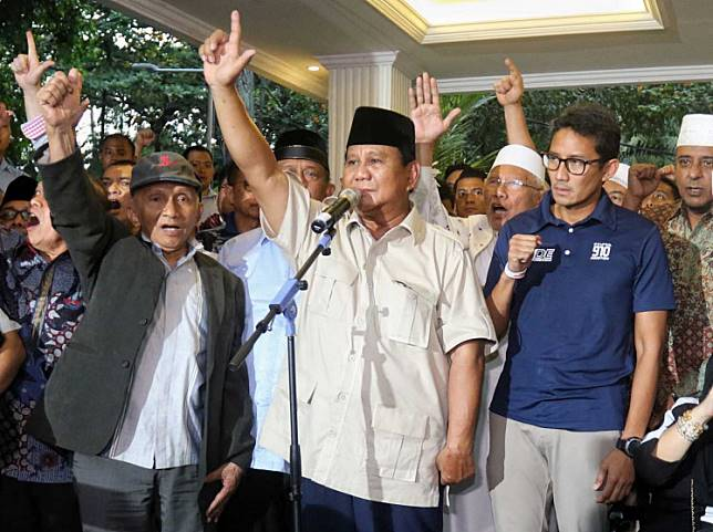 Rival candidate Prabowo Subianto (center) and his running mate Sandiaga Uno (right) gesture as they declare electoral victory on April 18, 2019 – the day after election day – during a press conference in Jakarta.