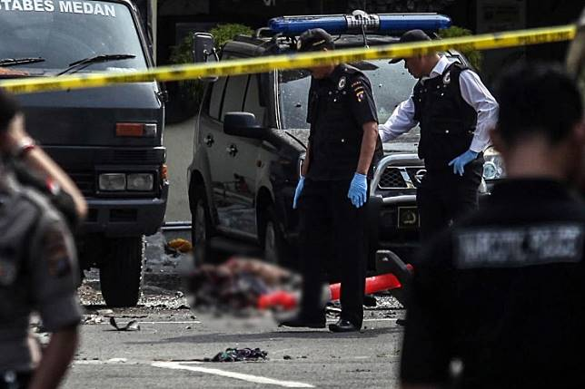 EDITORS NOTE: Graphic content. Indonesian police examine the body of a suicide bomber, identified as Rabbial Muslim Nasution, at their headquarters in Medan, North Sumatra, on Nov. 13. The attack occurred after the police's morning roll call.