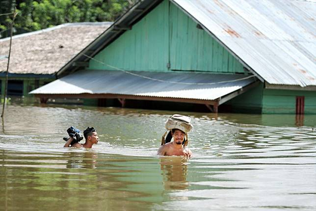 Two people wade through floodwaters in Tonduno village, South Konawe regency, Southeast Sulawesi, on Monday. Twenty-eight villages in 17 districts in the regency are reportedly inundated with floodwaters that have damaged thousands of homes and displaced 995 people, according to the local natural disaster mitigation agency.