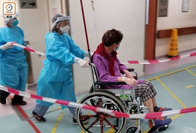 醫護人員拉起膠帶,護送一名病人上病房。(朱先儒攝)