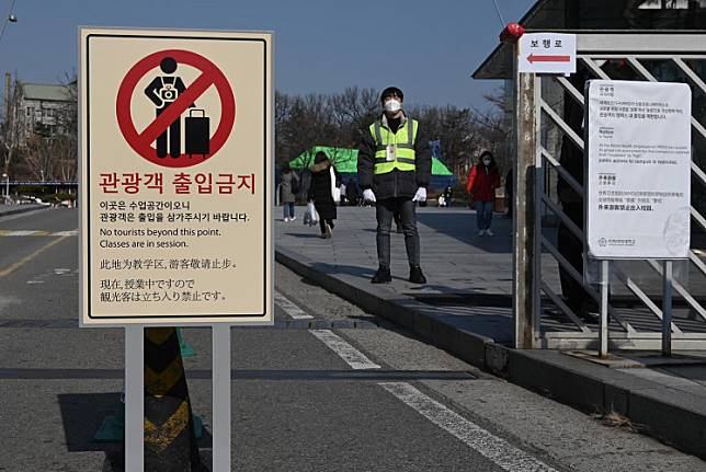 A security guard stands next to a 'no tourists' sign amid concern over the spread of the SARS-like virus, at the main entrance of a university in Seoul on Feb. 4. South Korea reported 20 new confirmed cases of the novel coronavirus on Wednesday -- increasing its total by nearly two-thirds -- including a cluster of at least 16 centered on the southern city of Daegu.