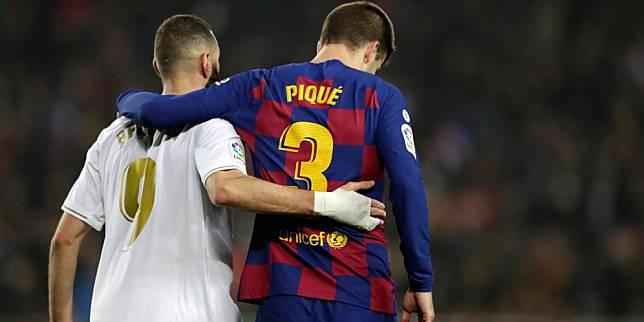 Bomber Real Madrid, Karim Benzema, bersama bek senior Barcelona, Gerard Pique usai duel El Clasico. (c) AP Photo