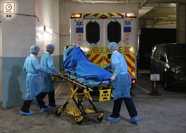 確診新冠肺炎的警員,其家人由醫護人員用擔架床抬上救護車。(余宏基攝)