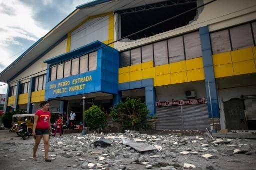 A resident walks past debris from a partially damaged building after a 6.4 magnitude earthquake hit the night before in the city of Digos, Davao del Sur province on the southern Philippine island of Mindanao on October 17, 2019. A child was killed in the strong 6.4-magnitude quake that hit the southern Philippines on October 16, a local mayor said, as houses collapsed, power was knocked out and a shopping mall burst into flames.