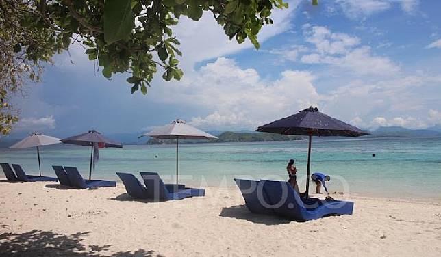Suasana pantai di Pulau Kanawa, Labuan Bajo, Manggarai Barat. Berpasir putih dengan kursi-kursi malas dan payung. TEMPO/Rita Nariswari