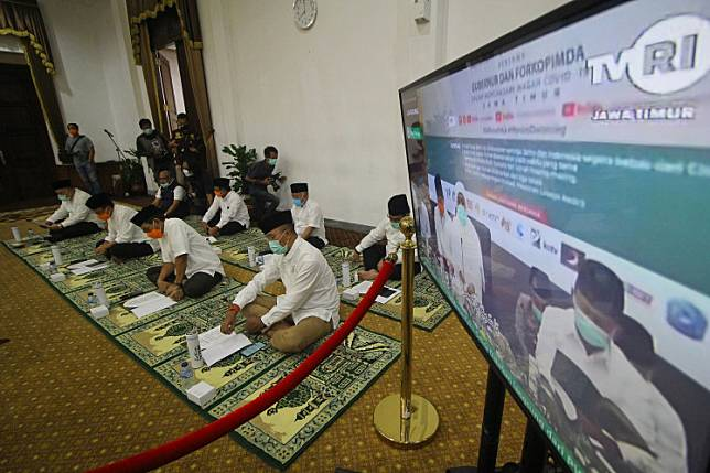 Representatives of the East Java Regional Leadership Communication Forum (Forkopimda) attend an online Nisfu Syaban mass prayer from the Grahadi Building in Surabaya, East Java on April 8, 2020. Nineteen clerics led the one-hour online mass prayer to pray for God to lift the COVID-19 outbreak from the country.