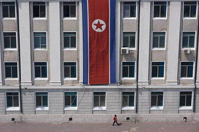 In a photo taken on April 12, 2019 a pedestrian walks past a North Korean flag displayed on a building in Pyongyang.