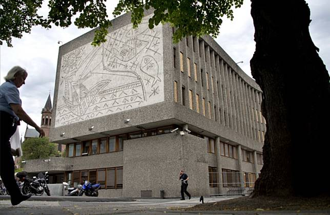 People pass Picasso's mural art work 'The Fisherman' on the government quarter's 'Y building' in Oslo, Norway on August 6, 2013.