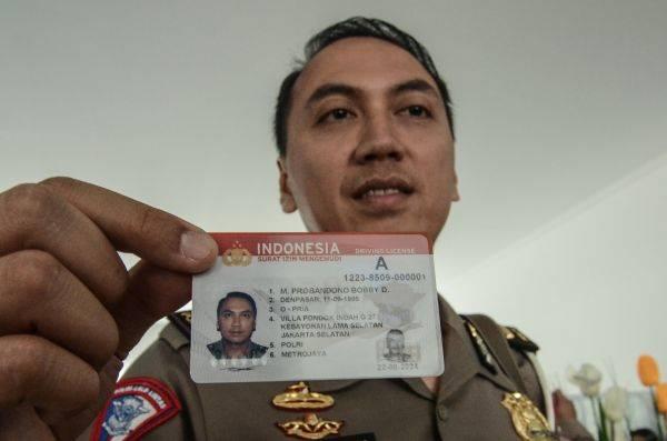 Polisi menunjukkan kartu Smart SIM (Surat Izin Mengemudi) di Gedung Satuan Penyelenggara Administrasi (Satpas), Kabupaten Bekasi, Jawa Barat