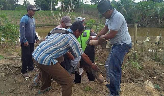 Petugas kepolisian bersama warga mengangkat korban tewas akibat bentrok di Register 45 Kabupaten Mesuji, Lampung, 17 Juli 2019. Bentrokan dipicu mengenai lahan garapan di wilayah hutan register 45 Mesuji. Istimewa