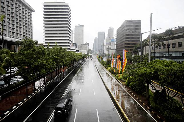 A vehicle passes a mostly empty and wet Jl. MH Thamrin in Central Jakarta on Jan. 1. Less traffic was reported on several main thoroughfares in the capital on the first day of 2019.