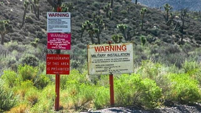 Rambu berisi peringatan terpancang di sekitar pagar Area 51 di Nevada, Amerika Serikat. [Shutterstock]