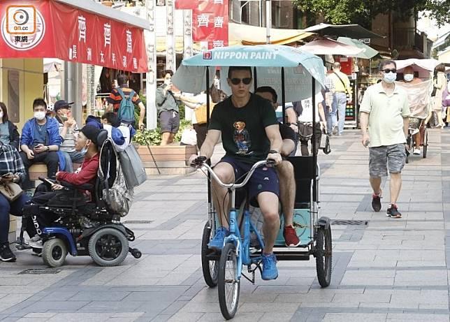 長洲街上騎單車的市民未有戴好口罩。(袁志豪攝)