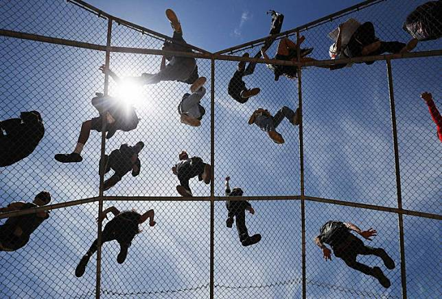 Protestors listen to speeches from atop a baseball backstop during a Black Lives Matter demonstration following the death of George Floyd on May 30, 2020 in Los Angeles, California.An attorney for George Floyd vowed at a memorial service on Thursday to find justice for the African-American man whose harrowing videotaped death while being arrested last week sparked nationwide protests.