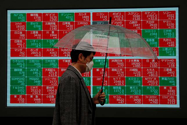 A visitor wearing protective face mask, following an outbreak of the coronavirus, walks past in front of a stock quotation board outside a brokerage in Tokyo, Japan on March 2, 2020.