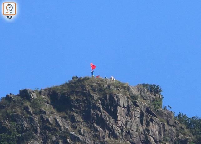 有人在獅子山上揮舞五星旗。(曾志恆攝)