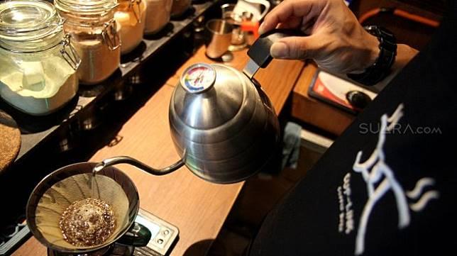 Seorang barista meracik kopi di salah satu kedai kopi di Jakarta, Selasa (5/3). [Suara.com/Arief Hermawan P]