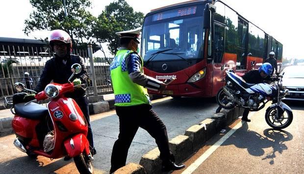 Petugas kepolisian memberhentikan sejumlah pengendara motor yang memasuki jalur busway di depan stasiun Jatinegara, Jakarta Timur, 8 September 2014. TEMPO/Dasril Roszandi