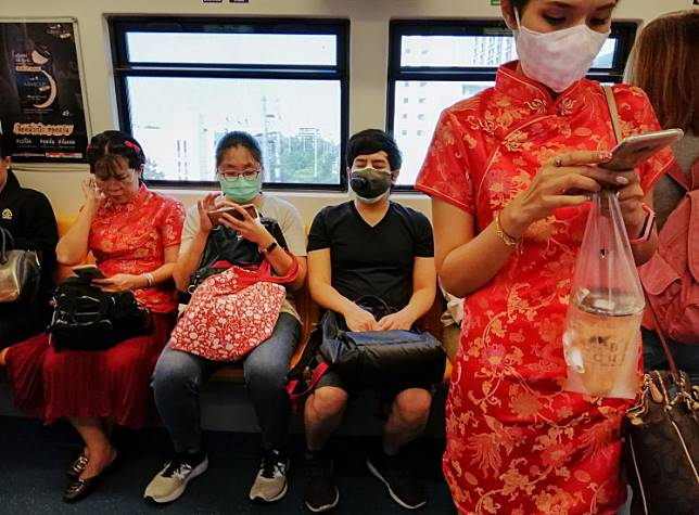 A woman with a face mask wears a cheongsam ahead of the Chinese Lunar New Year in a train in Bangkok on January 24, 2020, after four people were detected with the Coronavirus in Thailand.