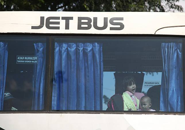 Two children wait for their bus to depart for their parents' hometown at the Kampung Rambutan bus terminal in East Jakarta on May 28, 2019.