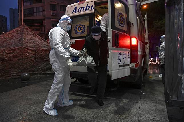 Medical staff members wearing protective clothing to help stop the spread of a deadly virus which began in the city, arrive with patients at the Wuhan Red Cross Hospital in Wuhan on January 25, 2020.
