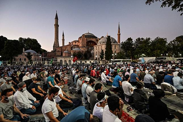 People, some wearing face masks, pray outside the Hagia Sophia museum in Istanbul on July 10, 2020 as they gather to celebrate after a top Turkish court revoked the sixth-century Hagia Sophia's status as a museum, clearing the way for it to be turned back into a mosque.