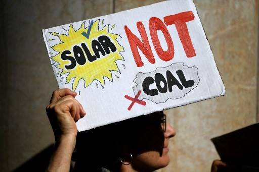 An environmental activist from Extinction Rebellion takes part in a protest against the India-backed Adani coal mine project, outside the GHD engineering office building in Sydney on August 13, 2019. Scores of environment advocates occupied the GHD Sydney offices to urge the engineering consultancy group to reject partnership with Adani.