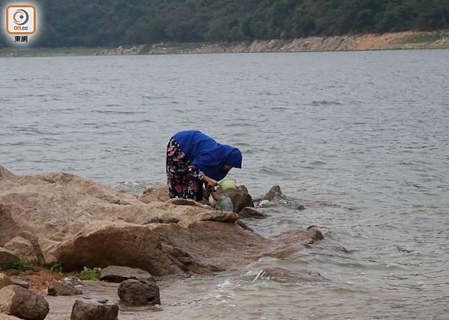 有露營人士在船灣淡水湖盛水清潔用具。