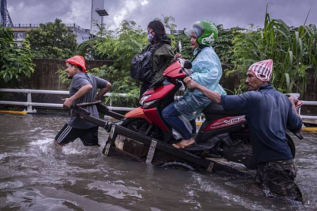 Novel commute: Two men use a cart to carry a motorcycle, its ride-hailing driver and her passenger through floodwaters on the morning of Feb. 25 in Grogol, Jakarta.